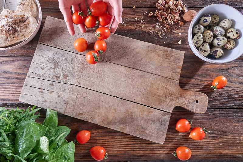 A set of ingredients quail eggs fresh herbs nuts boiled meat on a wooden table. The hands of the girl put tomatoes on the kitchen board with a copy space. Cooking dietary salad. Flat lay photo