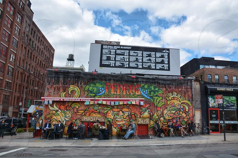 group of people sitting near graffiti wall photo