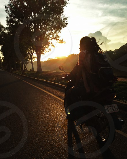 Girl riding on back of a motorcycle into the sunset photo