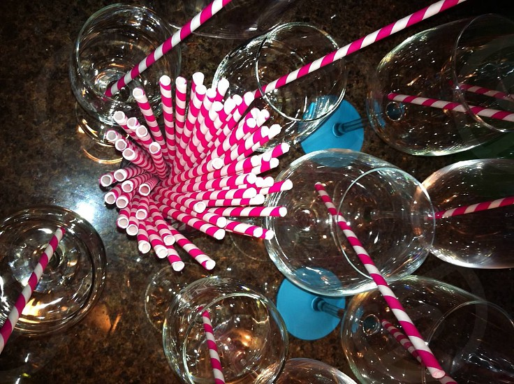 pink and white straws with clear wine glasses photo