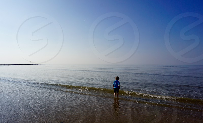 Boy by the Sea Coastal Scene                                photo