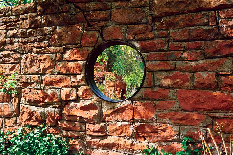 View through a round window of the only remaining wall of the Mayhew Lodge in the Call Of The Canyon recreational area near Sedona Arizona. photo