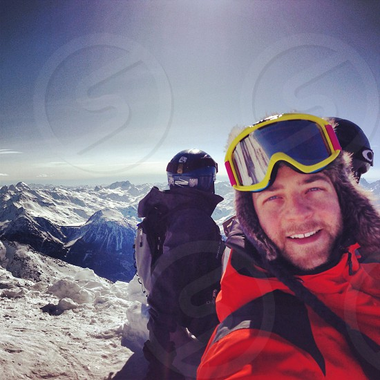 skier with yellow goggles wearing red ski jacket photo
