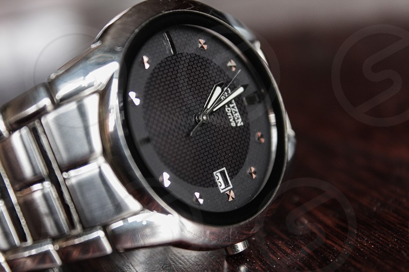 silver and black round citizen analog watch reading 11:00 photo