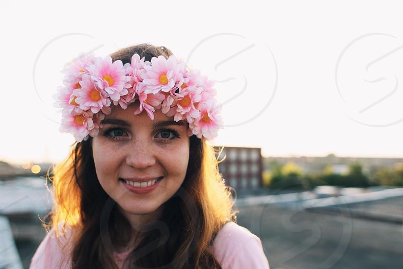 woman in white crew neck shirt wearing white flower crown photo