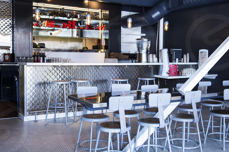 white and brown wooden bar stools in front of stainless steel counter photo