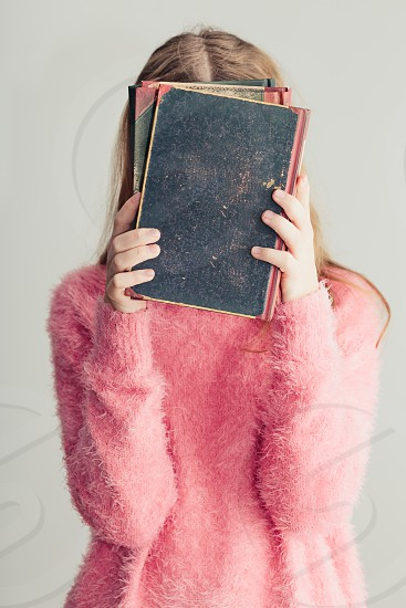 Young girl holding books in front of her face. Teenager girl wearing pink sweater. Vertical photo photo