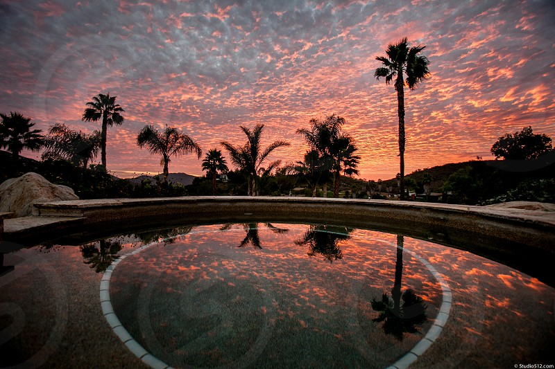 A sunset over a southern California hot bub.  Reflection sky silhouette pool palm trees clouds. photo