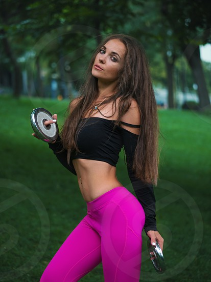 Beautiful sexy young caucasian woman in fitness wear working out in a park. Lady with long hair and sexy outfit doing sport exercises with sports weight in the forest in summer. photo
