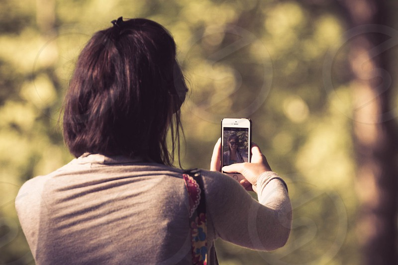 Woman takes selfie in the park photo