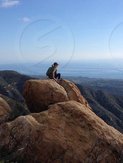 woman in green top sitting on brown rock formation during daytime photo