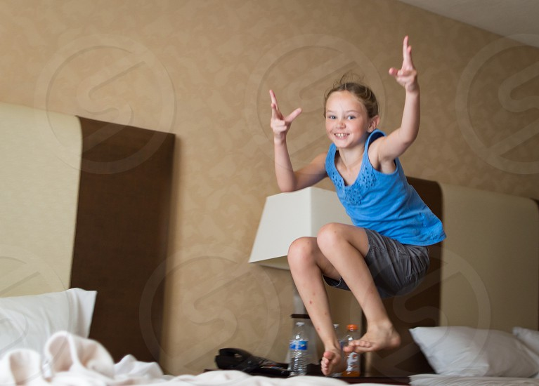 girl in tank top jumping on the bed photo
