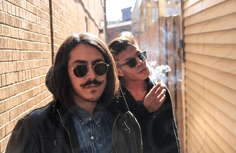 man wearing black sunglasses blue denim shirt with black leather jacket with mustache beside man in black jacket smoking photo