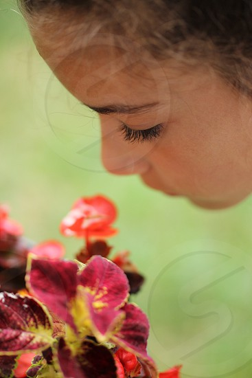 girl with black eyelashes near red and yellow leaf plant photo