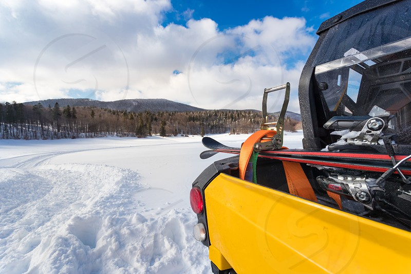Adult man tie down ski equipment on vehicle using straps and ratchet on snowy surrounding   photo
