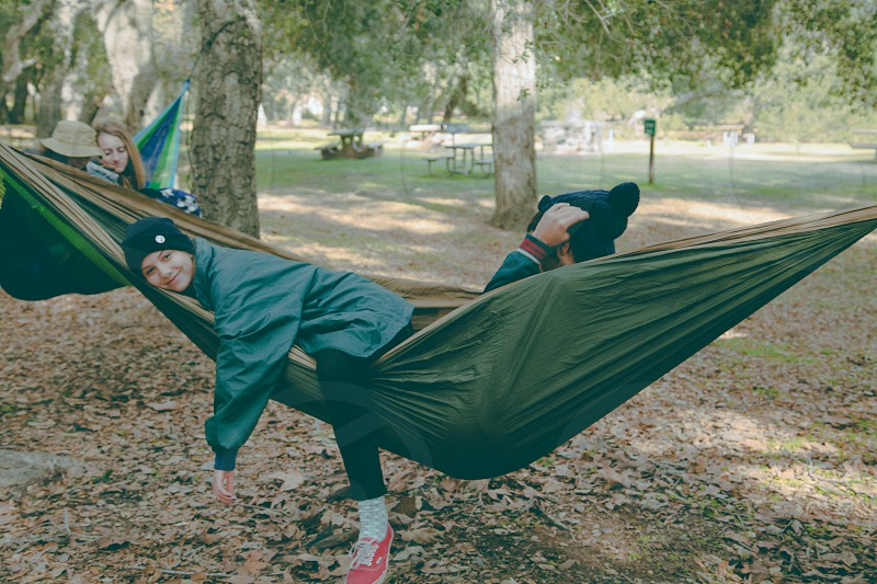 4 people in 2 green hammocks attached to trees photo