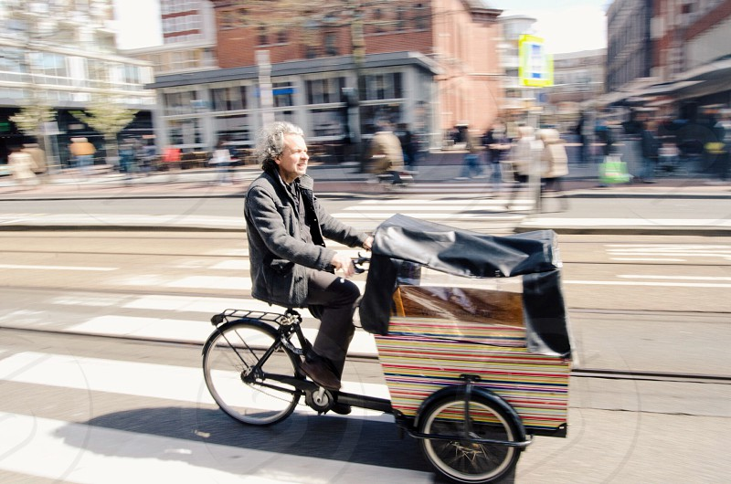 man in gray coat riding trike near pedestrian street during daytime photo