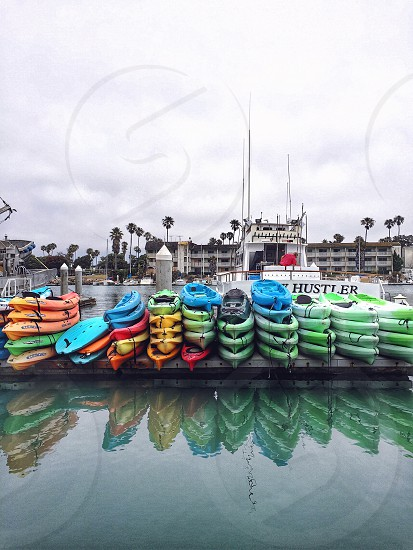 blue green red and yellow kayaks on wooden dock under white cloudy sky photo