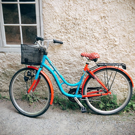 Red and blue bicycle with polka dot seat leaning against old brick wall stockholm photo