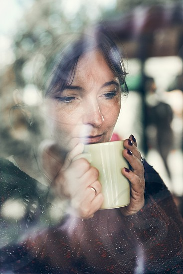 Portrait of woman drinking a coffee. Real people authentic situations photo