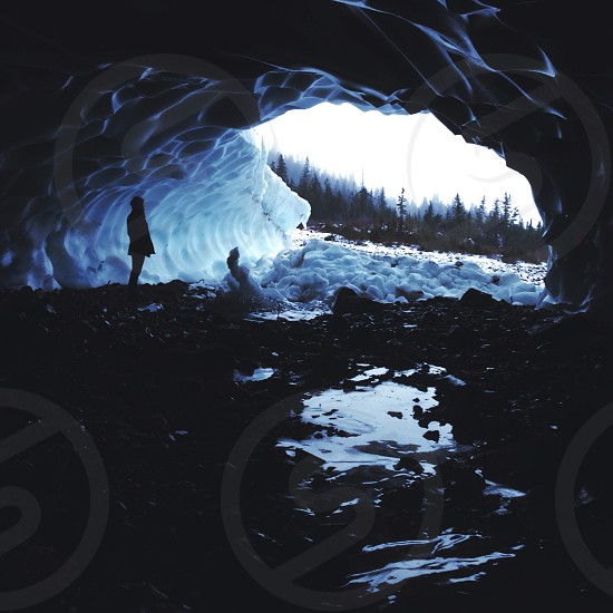 silhouette of person standing near mouth of snow covered cave photo