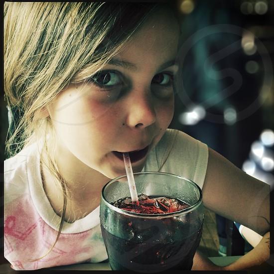 girl wearing white and pink shirt drinking black liquid photo