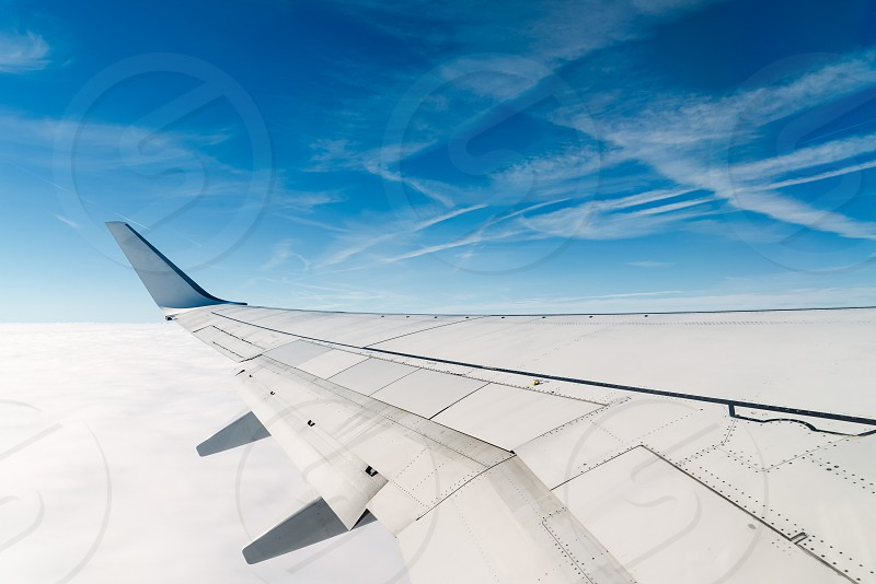 Airplane wing during flight against blue sky with white clouds photo