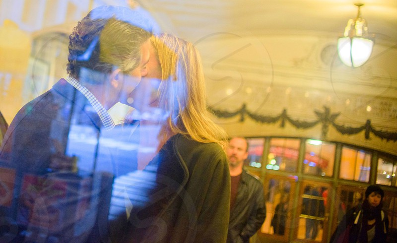 kissing couple inside glass window of lighted room photo