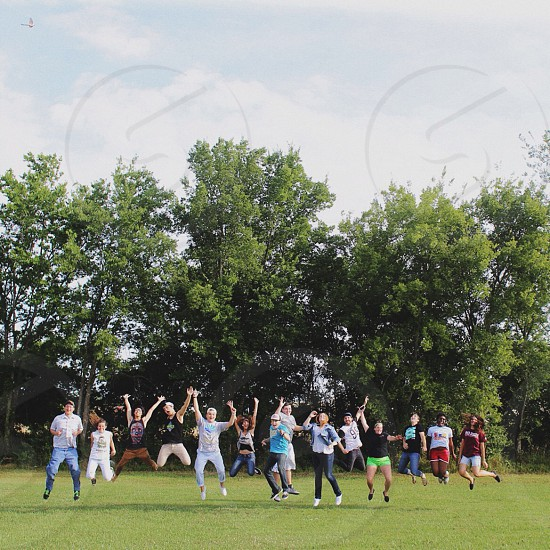 group of people jumping on a lawn photo