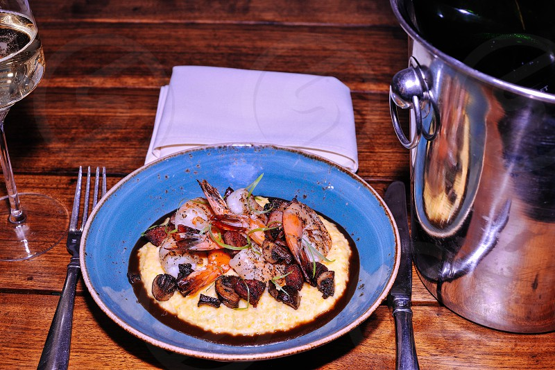 prawns and meat with sauce in blue ceramic round plate between stainless steel fork and stainless steel knife near stainless steel bucket photo