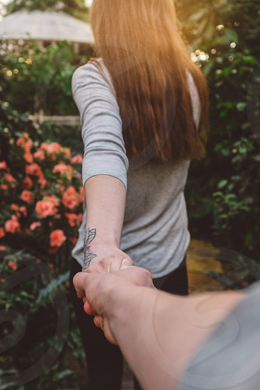 woman in gray 3/4 sleeve shirt with black left forearm tattoo holding man's hand at garden during daytime photo