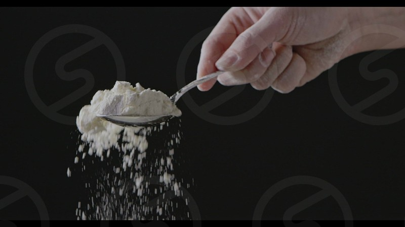 Natural flour is falling from spoon in a girl's hand on a black background. Slow motion Full HD video 240fps 1080p. Process preparing of homemade pastry. photo