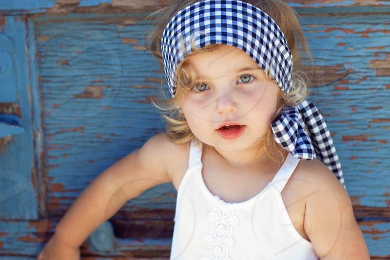 Beautiful blue eyed little girl against a blue door. photo
