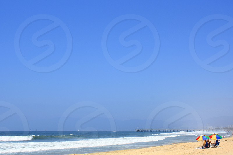 Tiny umbrellas are seen in the distance on a sandy beach near the ocean photo