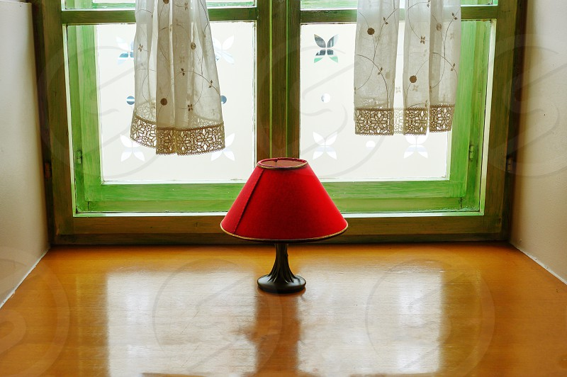 Vintage red lamp with shade on window intimate indoor scene reflection in hardwood window shelf decoration and design concept photo