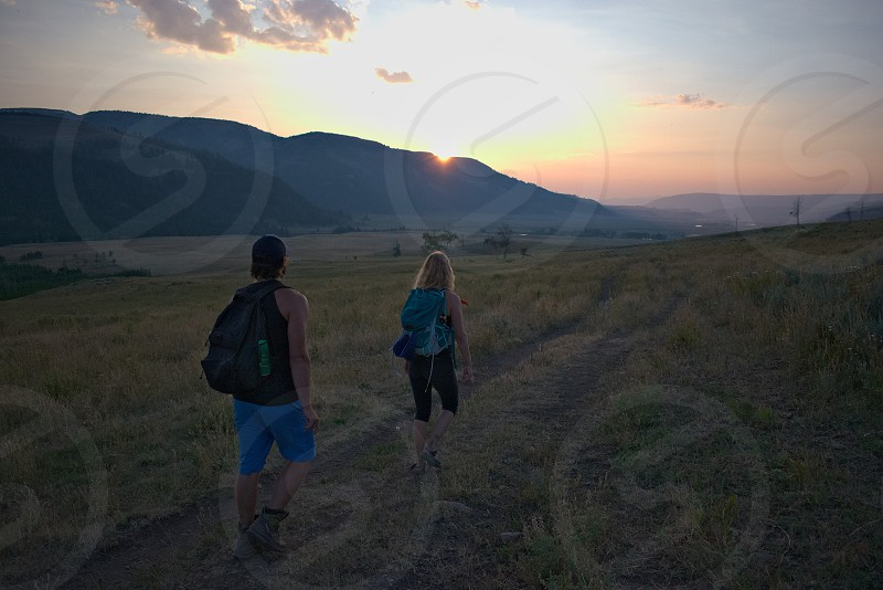Friends walking through Yellowstone National Park at dusk. photo