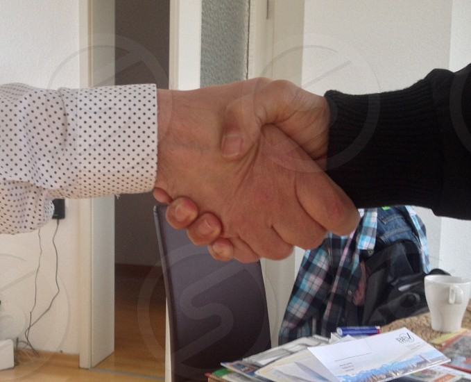 2 person doing shaking hands on white room photo