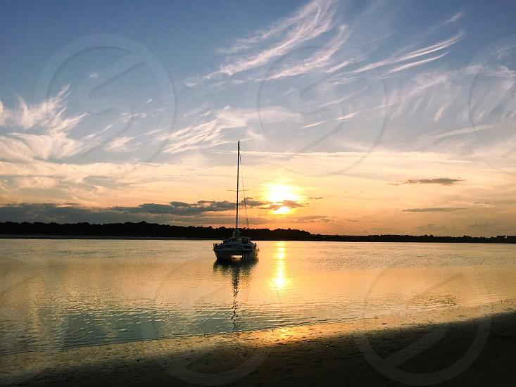 Landscape filter adjust warmth and exposure. Matanzas Inlet Florida sunset sailboat.  photo