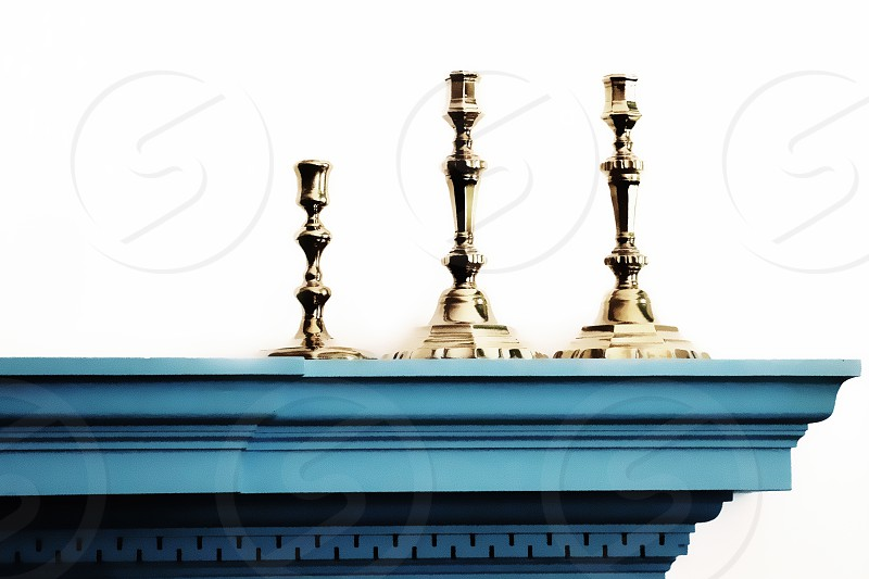 Three gold colored candlesticks stand on a blue fireplace mantle against a white background photo