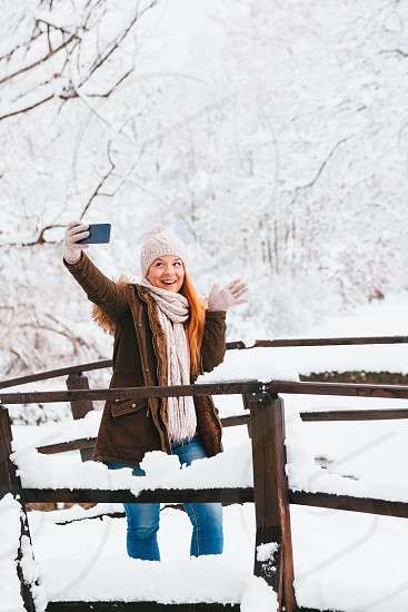 Young woman taking a selfie in a park on a snowy winter day photo