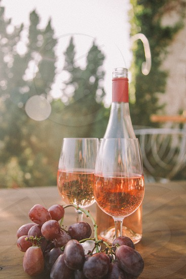 two wine glasses filled with rose wine on a table next to the bottle and purple table grapes with trees in the distance photo