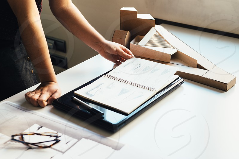 Close up of creative professional checking architectural model and notebook. photo