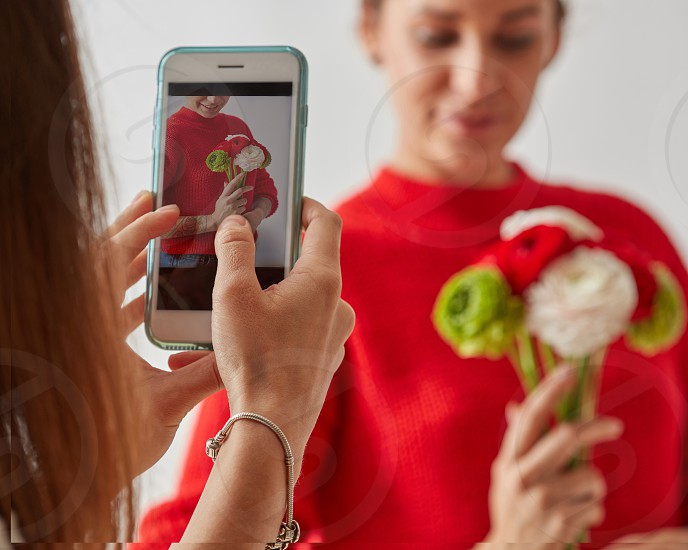 A woman with a mobile phone takes a photo of a girl in a red sweater with a bouquet of different colors on a gray background photo