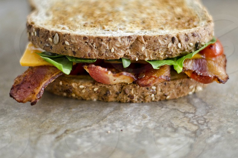 Sandwich food foodie blt healthy eat diet gourmet cheese bacon toasted wheat toast toast bread bread slices food and drink bacon sandwich fast food tomatoes vegetables deli. big cold. cafe lunch snack dinner up close closeup grain meal lettuce no body whole green yellow red brown leaf cut thin golden space copy  photo
