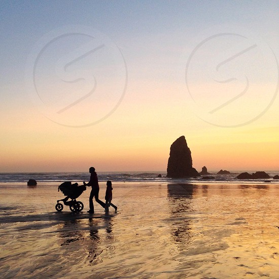 person pushing a baby stroller along the shore with a child following them photo