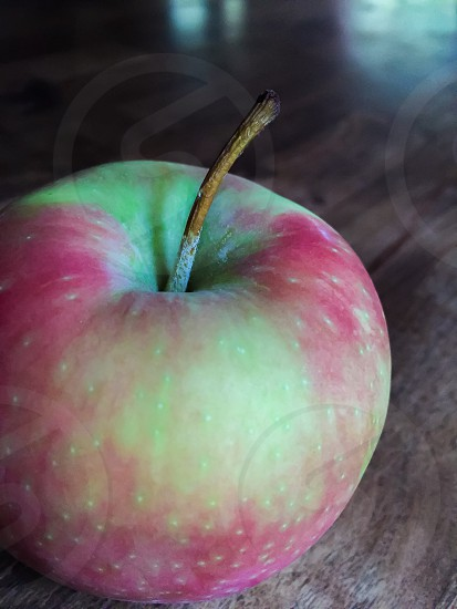 red apple on brown wooden tabletop photo