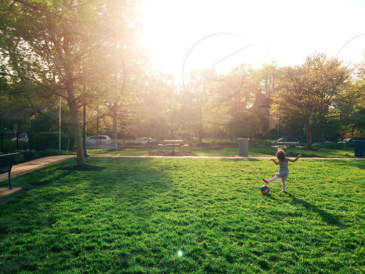 child playing with ball on green grass photo