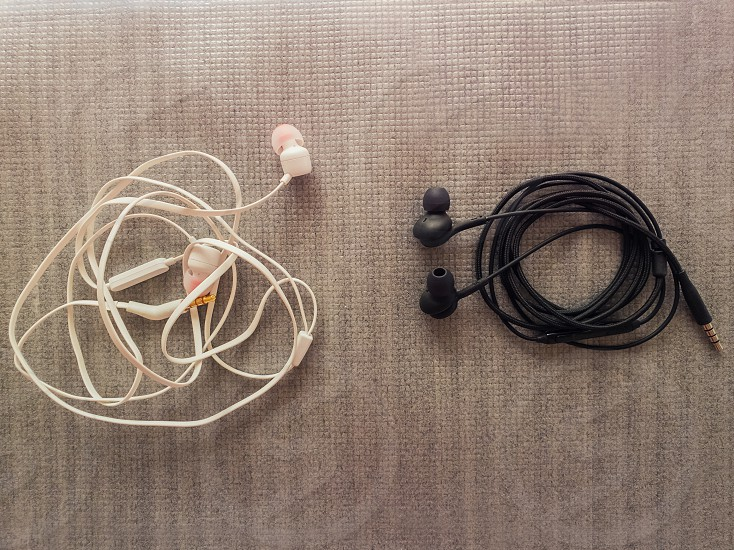 Two pairs of black and white wired headphones for music listening. Wrap different ways one is tangled while another neatly wrapped as a characteristic of different human behavior opposite concept. photo