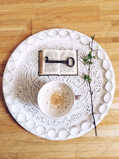 white tray holding a cup of coffee a twig a small book and a black key photo