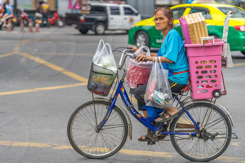 A senior lady cycling an overloaded bicycle in a busy Bangkok street. photo